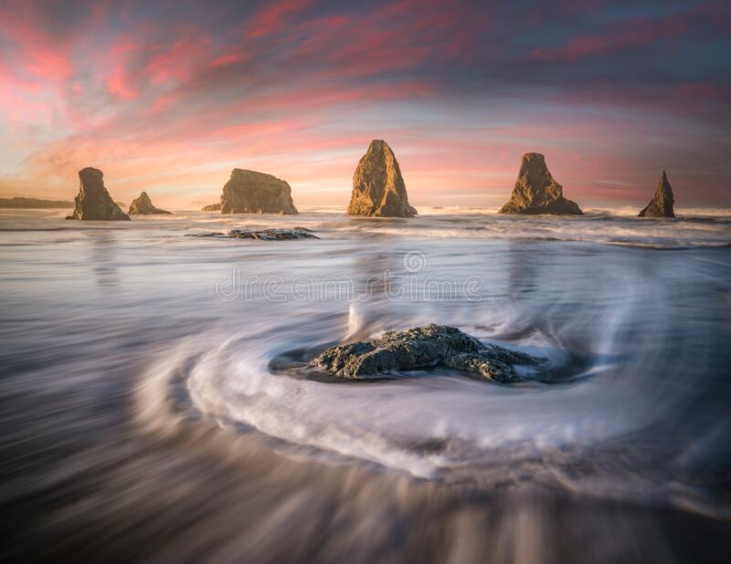 Soft sea streaks and sea stacks line up. This is a photograph of Silky sea streaks and sea stacks line up at dawn stock photos
