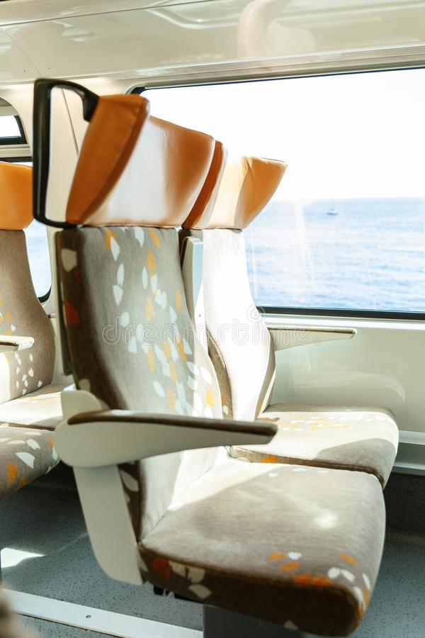 Soft seats in a comfortable train car. The route along the coast, outside the window a beautiful seascape. Bright sunny day. Vertical royalty free stock image