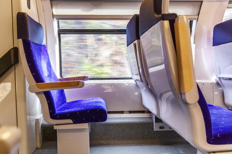 Soft seats in a comfortable train car. The route along the coast, outside the window a beautiful seascape. Bright sunny day. Horizontal royalty free stock photography