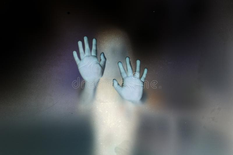 Haunted of ghost hands, Halloween concept. Soft shutter haunted of ghost hands behind the frosted glass negative film style, Halloween concept royalty free stock photography