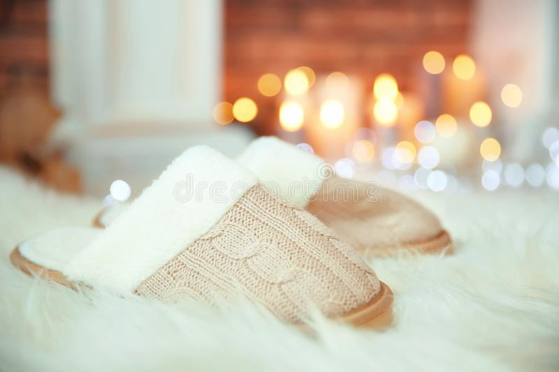 Soft slippers, fuzzy rug and blurred Christmas lights royalty free stock photos