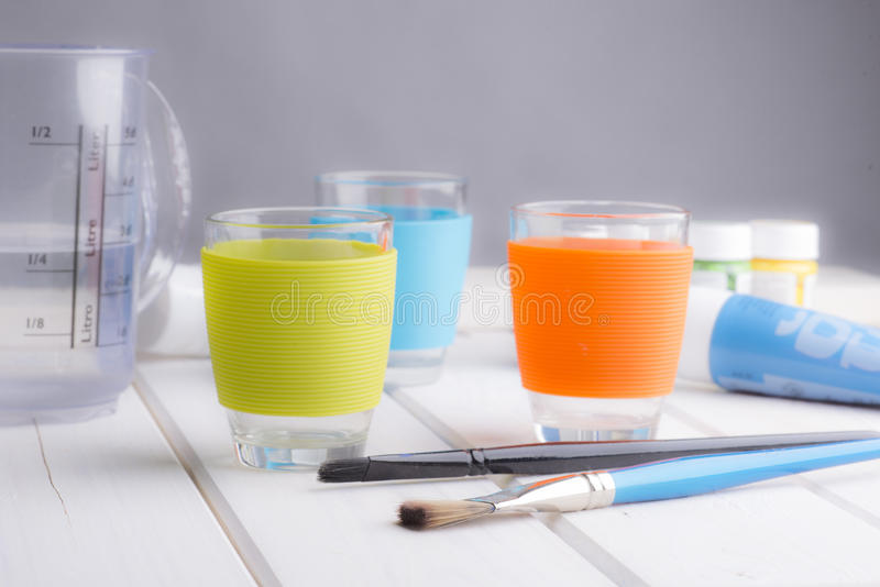 Soft still life of colorful cups, brushes and paint on a white wooden table. stock photography