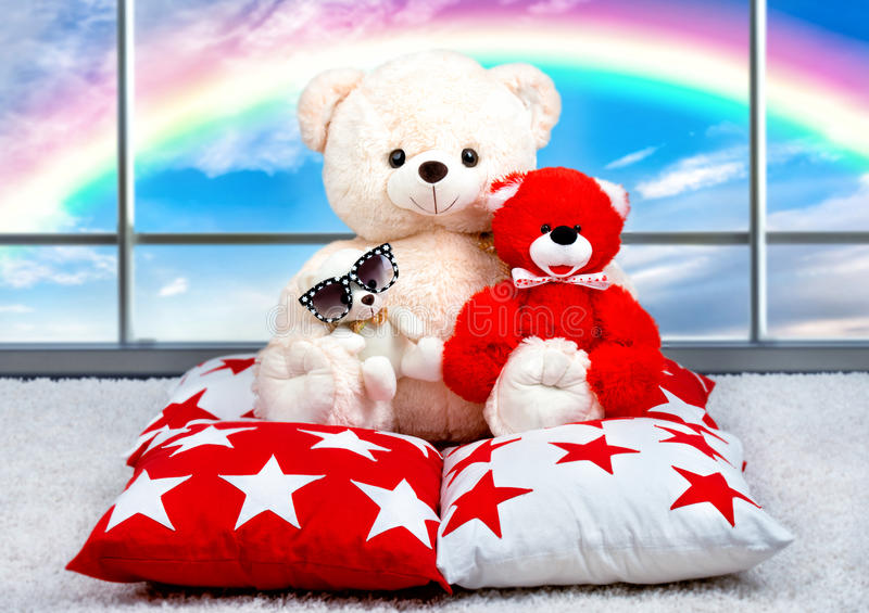 Soft Teddy bear sitting on the pillow on the background of the panoramic Windows.Rainbow. Soft toys,Teddy bears and cushions for interior decor stock photo