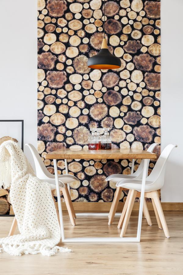 Soft textiles and log wallpaper. In impressive dining room with scandinavian decor, white chairs and wooden communal table stock photography