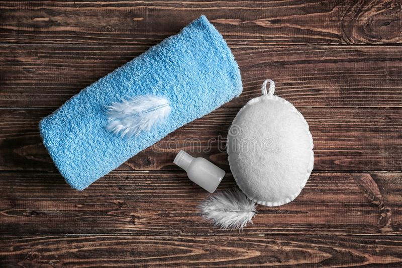 Soft towel and bath wisp and cream on wooden table royalty free stock photography