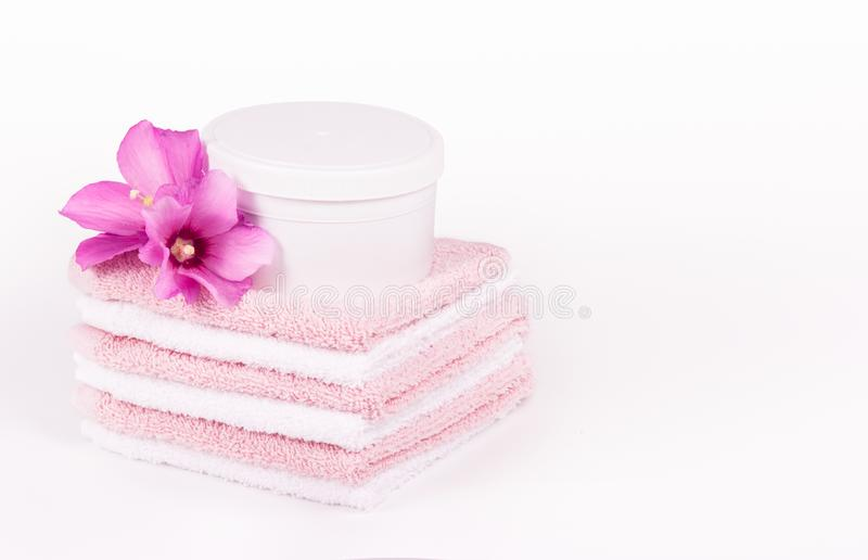 Soft towels and pink flowers. Mock-up jar spa cosmetics. Spa concept. Soft towels copy space royalty free stock photo