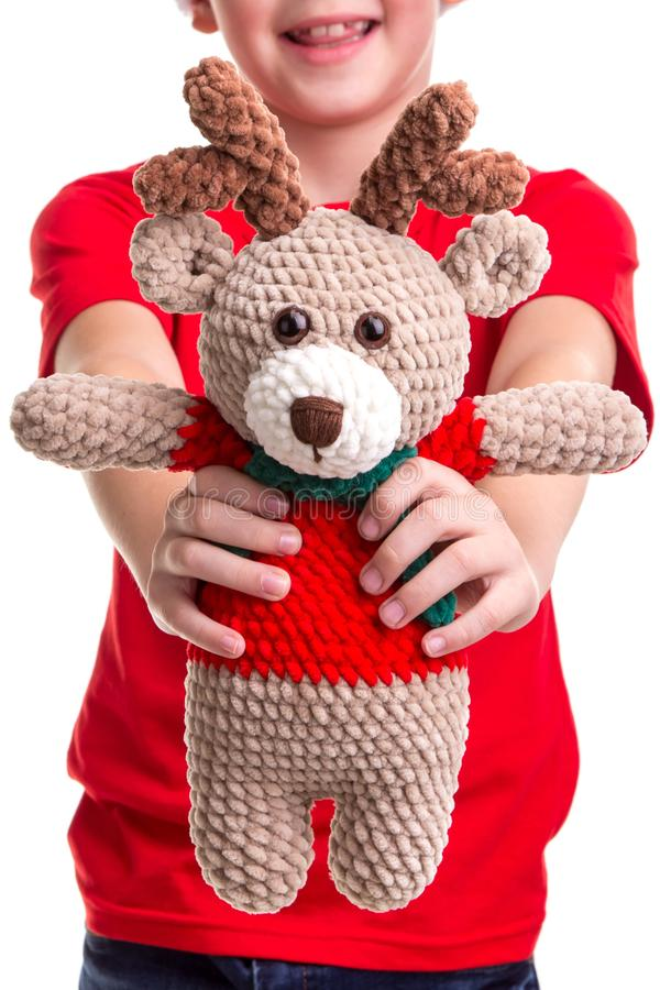 The soft toy of deer in the happy boy`s hands front view. Concept: christmas or Happy New Year holiday.  royalty free stock photos