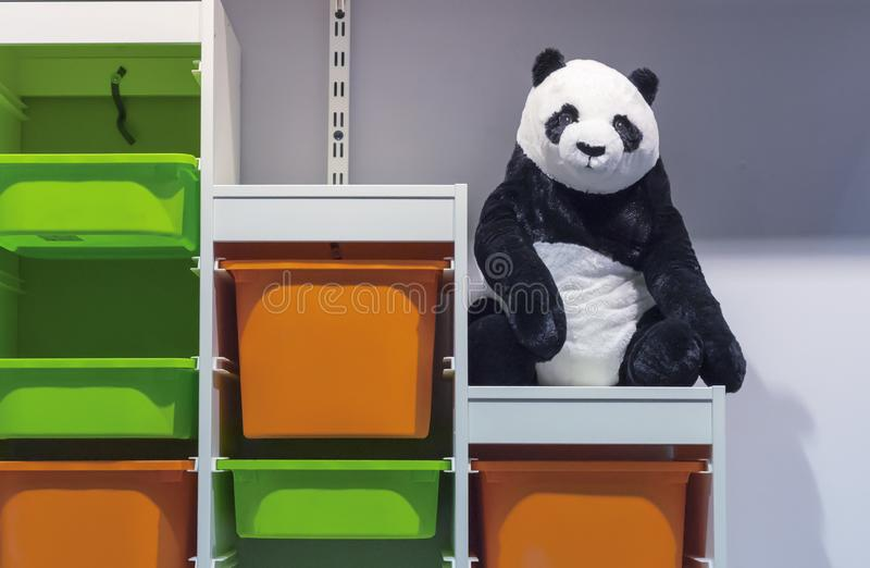 Soft toy panda on the rack with colored plastic boxes stock photos