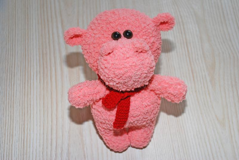 Soft toy pink Hippo stands on the table. stock image