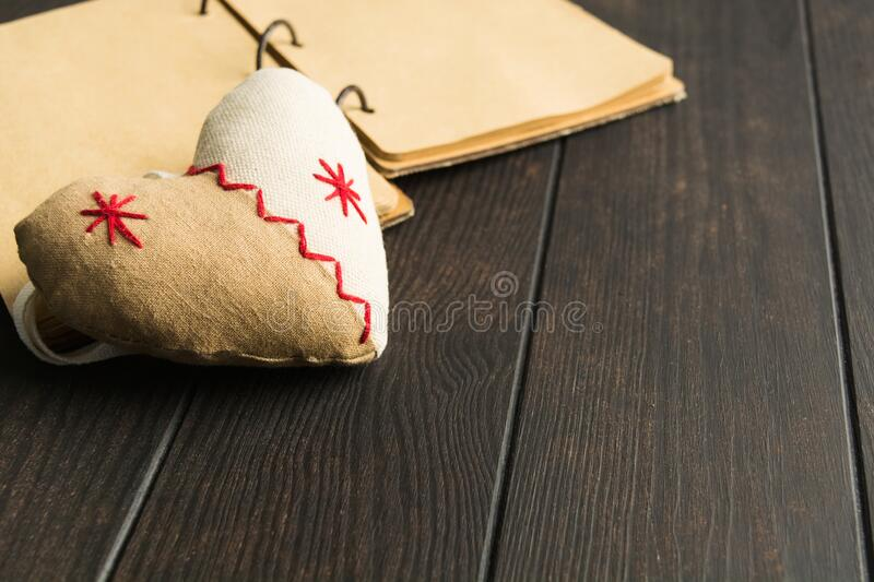 Soft toy with shape of heart with craft paper notebook over brown wooden table royalty free stock image