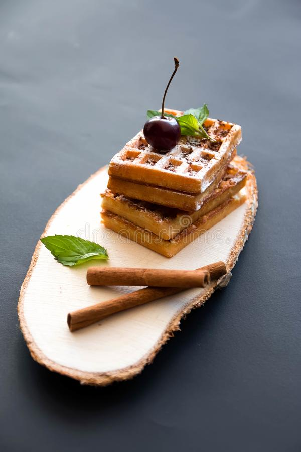 Soft waffles, on a black background, with cherries stock photo