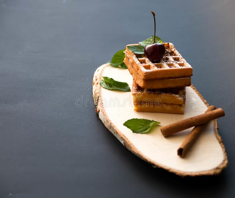 Soft waffles on a black background, with cherries royalty free stock photography