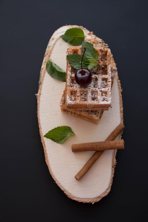 Soft waffles, on a black background, with cherries stock photos