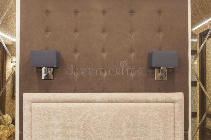 A soft wall and 2 sconces at the head of the bed between 2 mirrors - a symmetrical design. stock photo