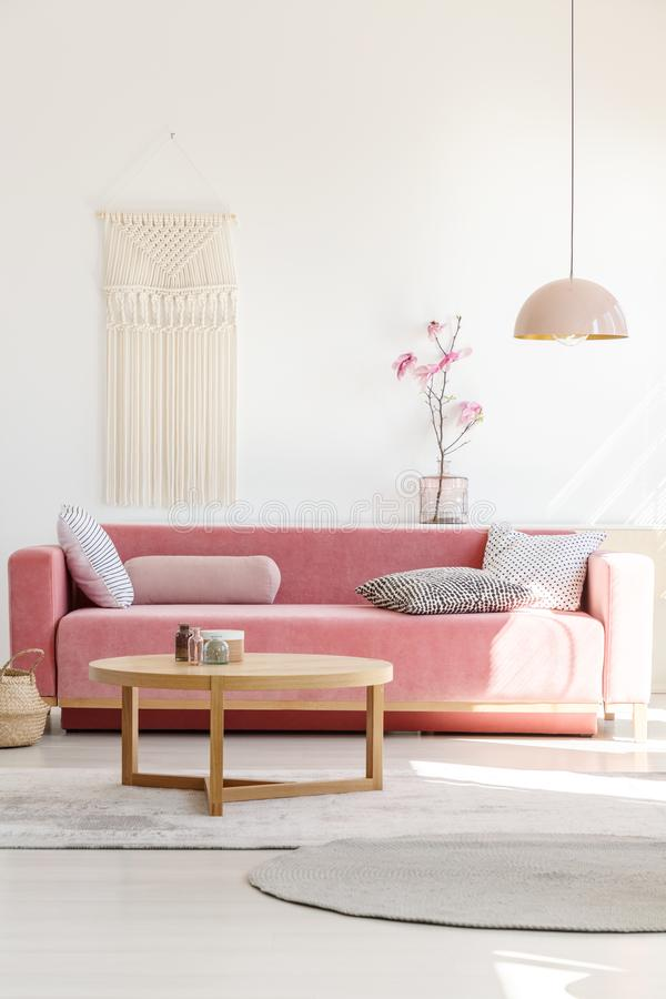 Soft, warm living room interior with a cozy, velvet sofa, millennial pink decorations and a beige macrame on a white wall royalty free stock photography