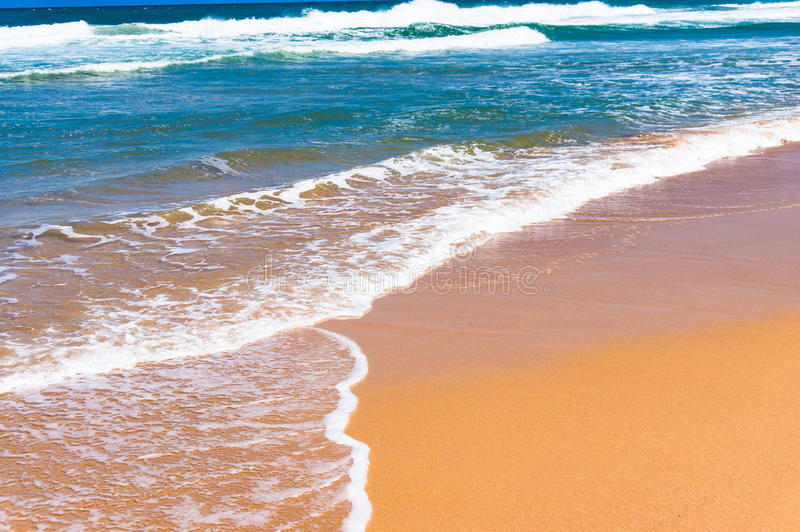 Soft wave of blue water on sandy beach. Seascape background stock photography
