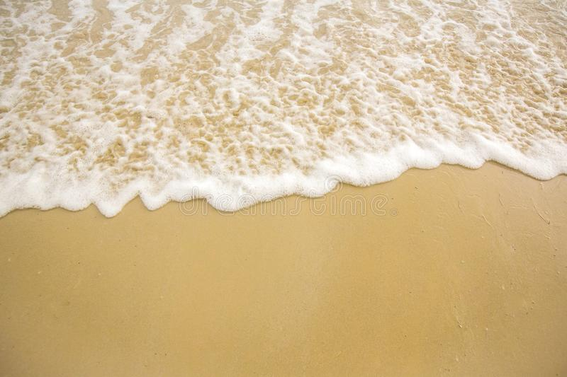 Soft Wave Ocean On Sandy Beach. Background. Selective focus.beach and tropical sea.white foam on beach. Soft focus on bottom of picture stock image