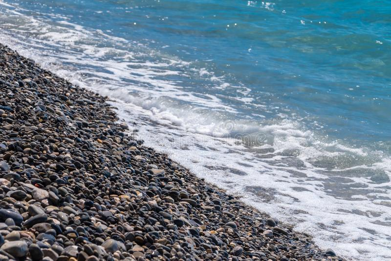 Soft waves on small pebble stones on seashore.  royalty free stock photo