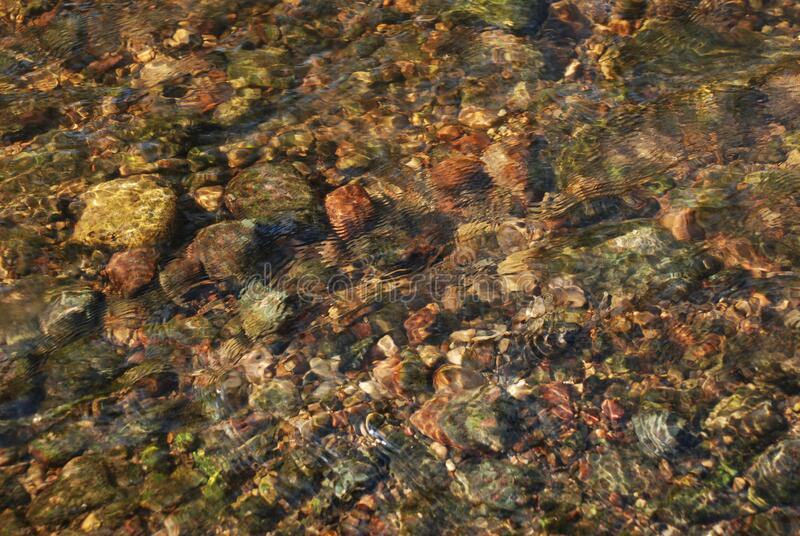 Transparent River flow on the stones and sand royalty free stock photo