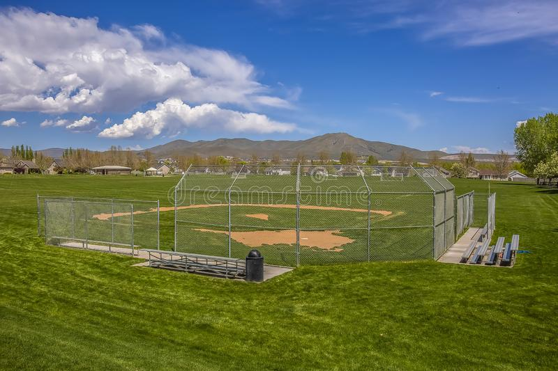 Softball or Baseball field with view of mountain and sky on a sunny day. Bleachers for players and spectators are installed behind the fence royalty free stock photography