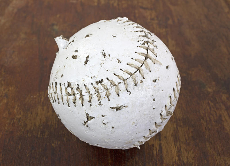 Softball that has been chewed on by dog. A softball that has been chewed and bitten by a dog on a wood background royalty free stock image