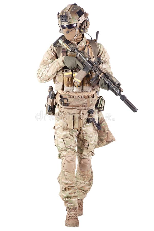 Softball player with military stuff studio shoot. Strikeball enthusiast in checkered shirt wearing military ammunition, face mask, helmet and radio headset royalty free stock images
