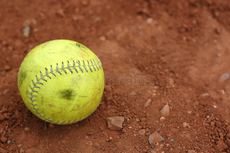 Softball, well used. A well used yellow softball on the infield dirt royalty free stock image