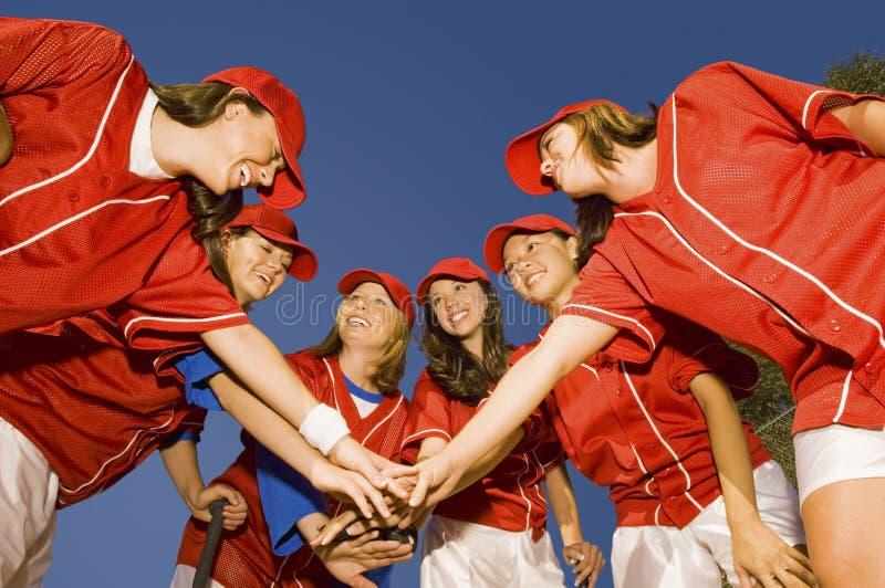 Softballspelare som staplar händer mot blå himmel royaltyfria foton