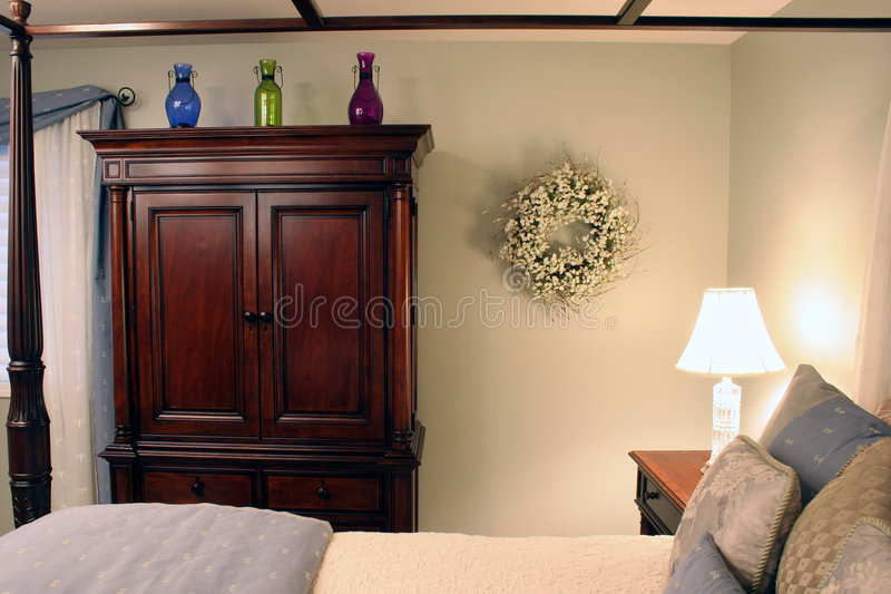 Softly lit bedroom. A warm and inviting bedroom softly lit with a crystal lamp stock photography