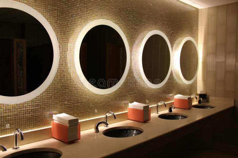 Softly lit mirrors in upscale bathroom royalty free stock images