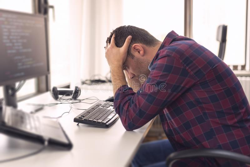 Software developer stressed out. Young software developer sitting at his desk at work, holding head in hands, stressed out because of failure and code royalty free stock image