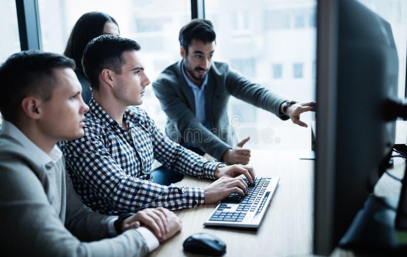 Software Engineers que trabalham no escritório no projeto junto fotos de stock