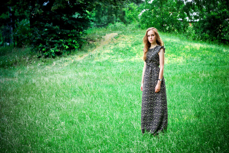 Soggiorni e sguardi tristi della donna alla macchina fotografica immagini stock