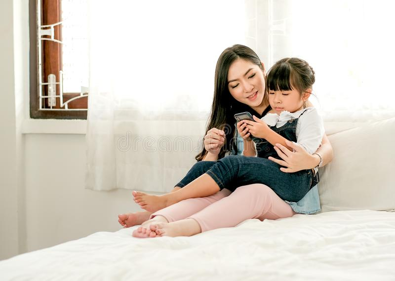 Soggiorno asiatico della figlia e della madre sul letto bianco e sguardo al telefono cellulare e godere di insieme fotografie stock libere da diritti