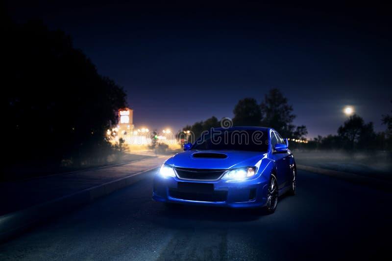 Soggiorno blu dell'automobile sulla strada della campagna dell'asfalto vicino alla città ed alla foresta alla notte della luna immagine stock