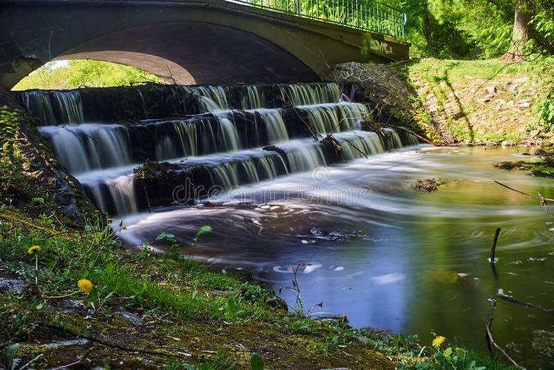 Soglia dell'acqua e del ponte sopra un piccolo fiume in un parco immagine stock libera da diritti