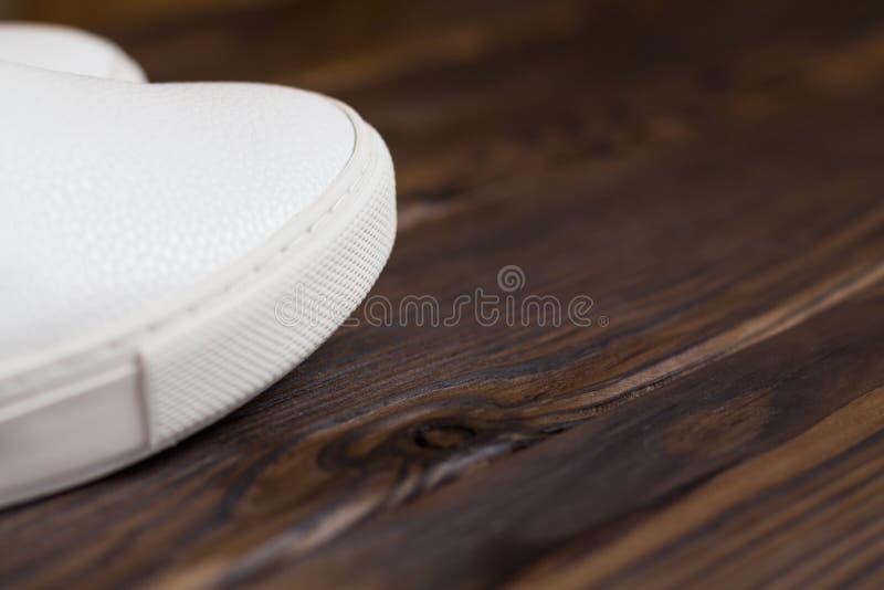 Sogliola delle scarpe da tennis bianche sul fondo di legno di marrone scuro vista della parte di sinistra, posto per testo, copys immagine stock