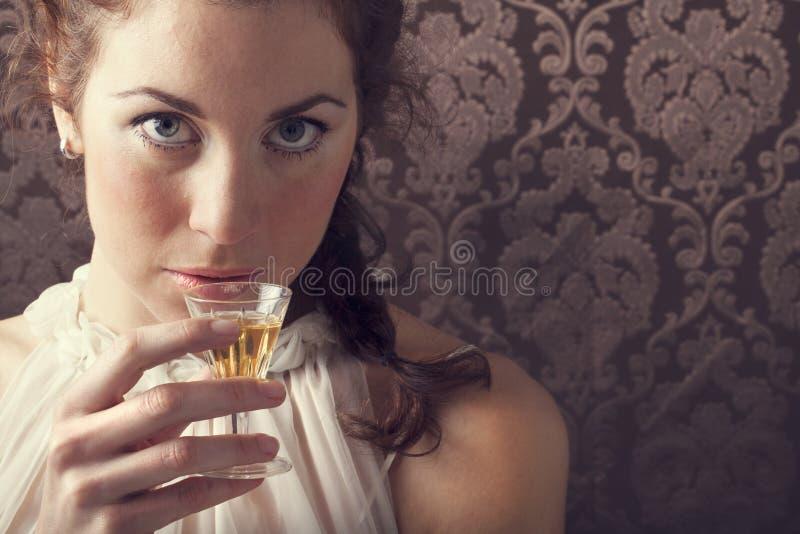 Sognando la donna beve un vetro di whiskey scozzese eccellente fotografie stock libere da diritti