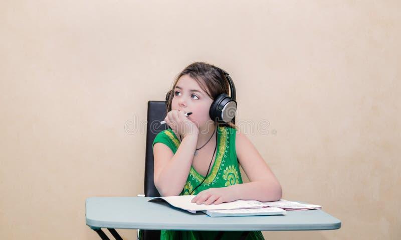 sognando piccola ragazza graziosa che si siede dietro una tavola e che distoglie lo sguardo con le cuffie sulla sua testa immagini stock libere da diritti
