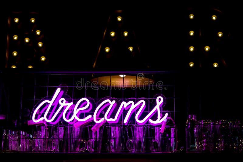 SOGNI al neon porpora e vetri dell'iscrizione sul fondo vago delle luci fotografia stock