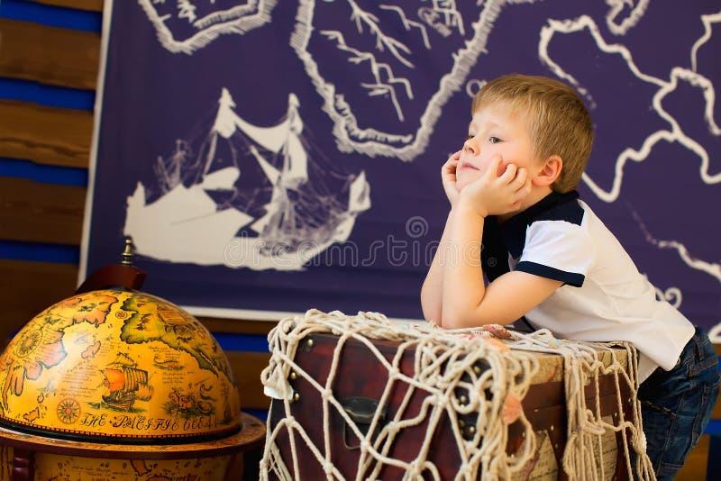 Sogni del ragazzo, sedentesi accanto al globo Viaggiatore futuro fotografia stock libera da diritti
