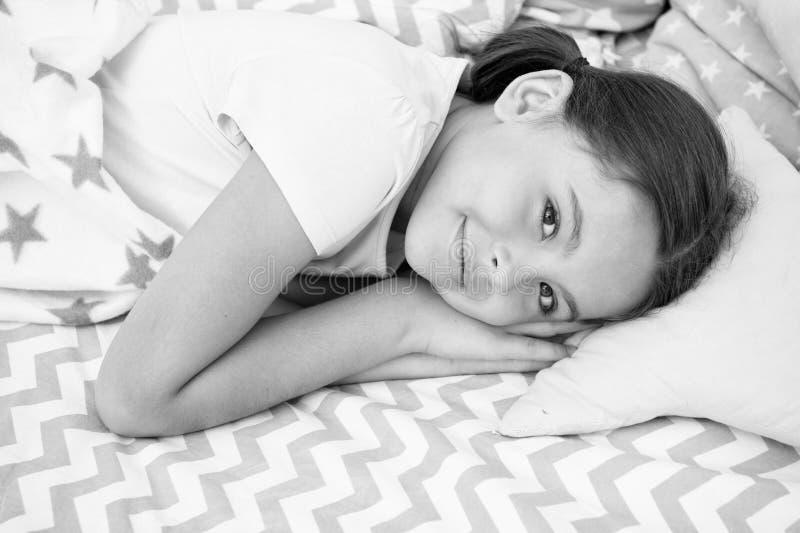 Sogni dolci Il bambino felice sorridente della ragazza mette sul letto con i cuscini del motivo a stelle ed il plaid sveglio nell immagine stock