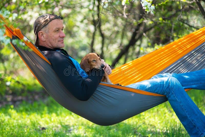 Sogno dell'uomo in un cappuccio con il suo cane divertente di sonno immagini stock libere da diritti
