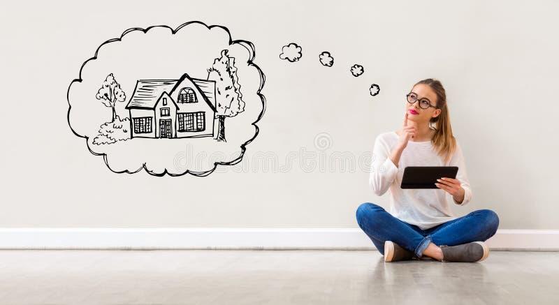 Sogno della casa nuova con la donna che per mezzo di una compressa fotografia stock libera da diritti