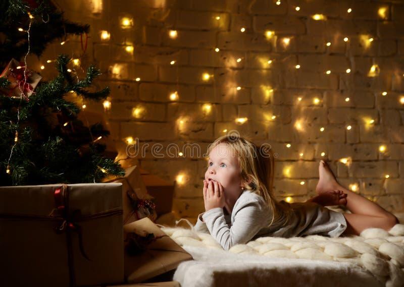 Sogno di menzogne della giovane neonata vicino ai regali magici del mestiere del nuovo anno da un albero di Natale immagini stock libere da diritti