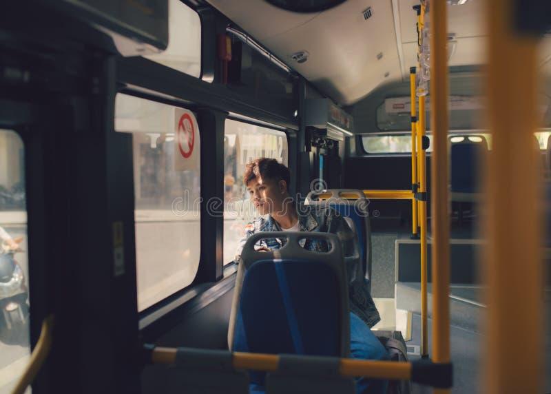 Sogno di seduta dell'uomo asiatico sul bus che guarda attraverso la finestra fotografia stock libera da diritti