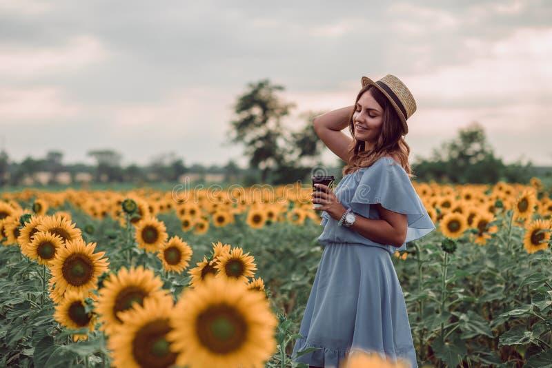 Sogno giovane donna in vestito blu e del cappello che tengono una tazza di caffè in un campo dei girasoli all'estate, vista dal s immagini stock libere da diritti