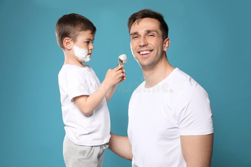 Sohn, der Schaum auf das Gesicht des Vatis rasierend zutrifft lizenzfreies stockfoto