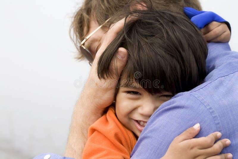 Sohn, der seinen Vater umarmt lizenzfreie stockfotografie