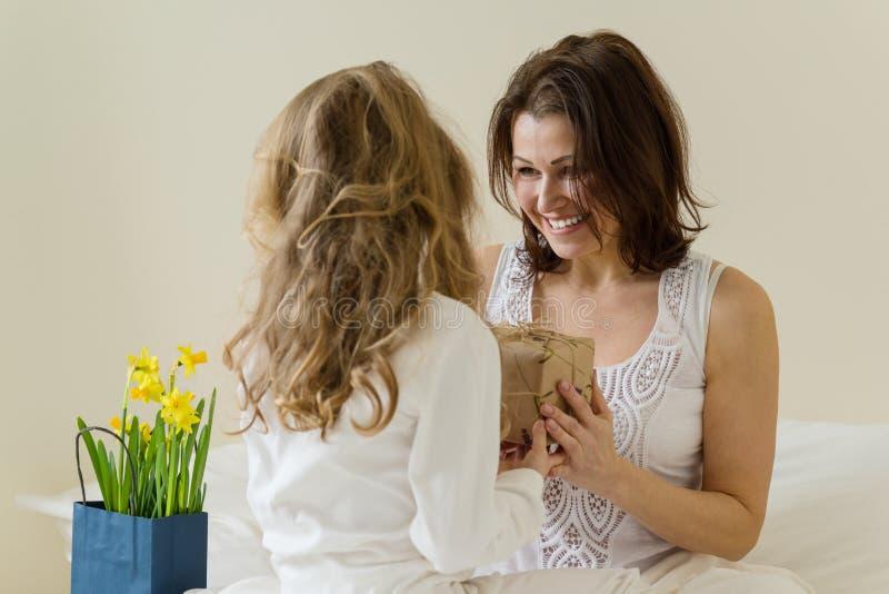 Sohn gibt der Mama eine Blume Die kleine Tochter hält ein Geschenk und Blumen für ihre Mutter Hintergrundinnenraum des Schlafzimm stockfotografie